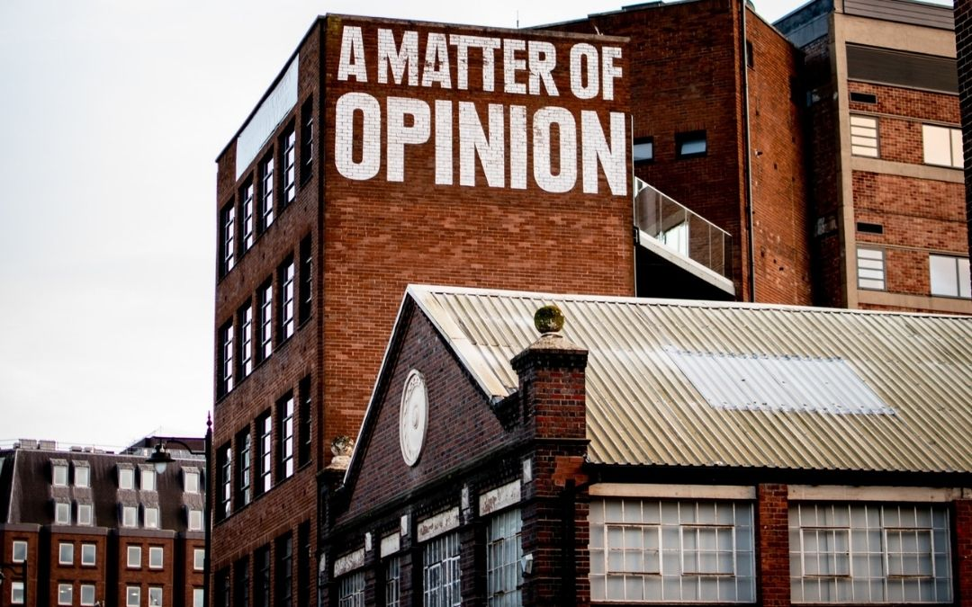 """Buildings with """"A Matter of Opinion"""" painted on wall"""