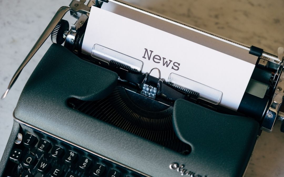 Grey traditional typewriter. White paper loaded with the word 'news' typed as large central heading.